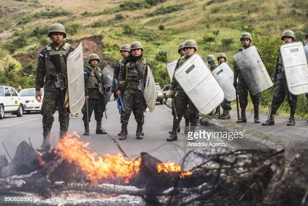 Honduran security forces stand guard on a road which was blocked by supporters of the opposition political party 'Alianza' due to the political...