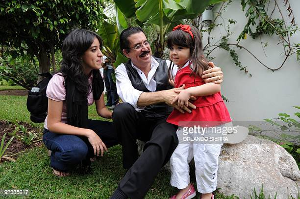Honduran toppled president Manuel Zelaya jokes with his granddaughter Irene while his daughter Hortencia looks on at the Brazilian embassy in...