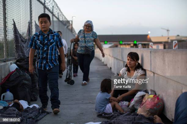 Honduran woman and her 2yearold daughter wait on the Mexican side of the Brownsville Matamoros International Bridge after being denied entry into the...