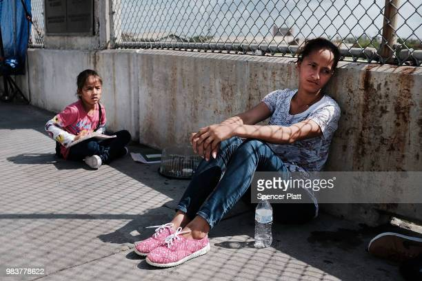 Honduran woman fleeing poverty and violence in her home country waits along the border bridge with her family after being denied entry into the US...