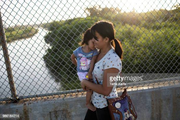 Honduran woman holds her 2yearold daughter as they wait on the Mexican side of the Brownsville Matamoros International Bridge after being denied...