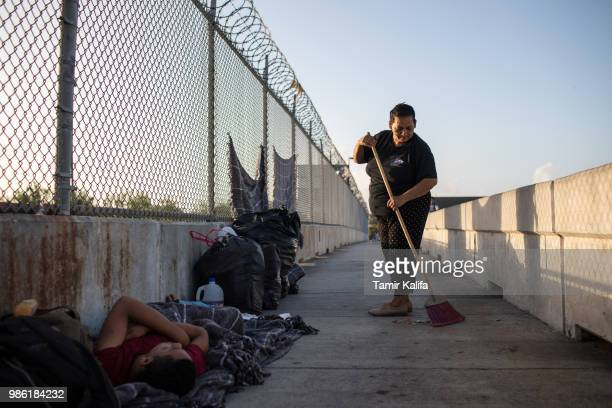 Honduran woman sweeps an area on the Mexican side of the Brownsville Matamoros International Bridge where she and her family have been waiting for...