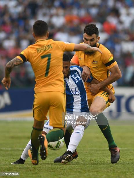 Honduras' Alex Lopez is marked by Australia's Josh Risdon and Mile Jedinak during the first leg football match of their 2018 World Cup qualifying...