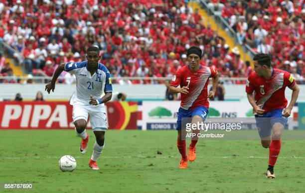 Honduras' Brayan Beckeles runs to elude Costa Rica's Christian Bolanos and Bryan Oviedo during their 2018 World Cup qualifier football match in San...