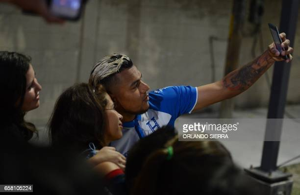 Honduras' football team player Mario Martinez poses for a selfie with residents of Chamelecon domain of Mara Salvatrucha and Barrio 18 gangs during...