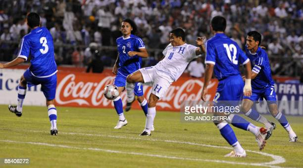Hondura's Julio de Leon kicks the ball past El Salvador's Marvin Gonzalez Alexander Escobar Manuel Salazar and Ramon Sanchez during their FIFA World...