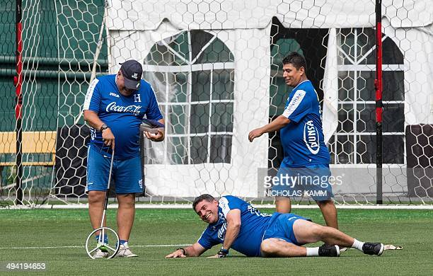 Honduras national team coach Luis Fernando Suarez jokes with members of his staff during a training session in Washington on May 28 2014 on the eve...