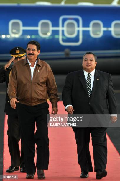 Hondura's President Manuel Zelaya reviews a honor guard with El Salvador's Vice Foreign Minister Luis Montes upon his arrival to El Salvador's...