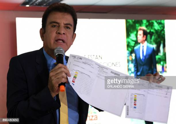 Honduras' presidential candidate for the Opposition Alliance against Dictatorship party Salvador Nasralla shows electoral records allegedly falsified...
