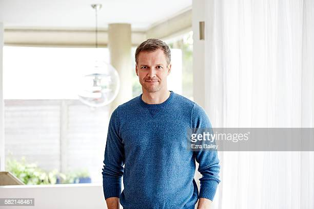 honest portrait of a man in apartment - long sleeved stock photos and pictures