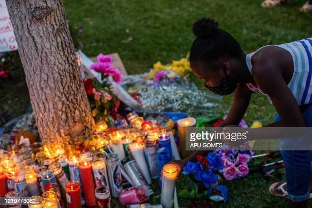 Honesty Strickland lights up a candel during a vigil around a makeshift memorial at the tree where Robert Fuller was found dead outside Palmdale City...