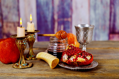 Honey, apple and pomegranate on wooden table over bokeh background 1013937104