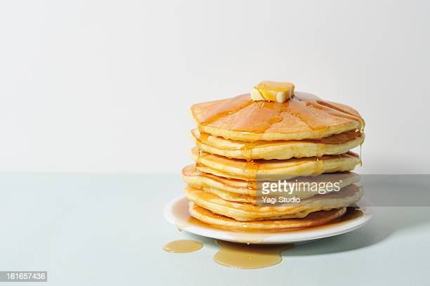Honey dripping syrup on pancakes