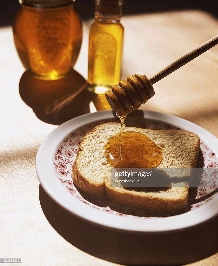 Honey Drizzler Dripping Honey On a Slice of Brown Bread : Stock Photo