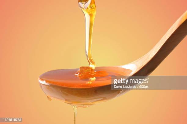 honey falling on wooden spoon with orange gradient background fr - help:ipa stock pictures, royalty-free photos & images