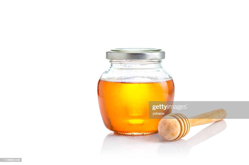 Honey in closed lid glass jar with wooden honey dipper at its side, all on white background with copy space : Stock Photo