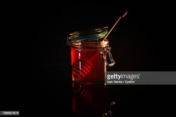 Honey In Jar With Dipper Over Black Background