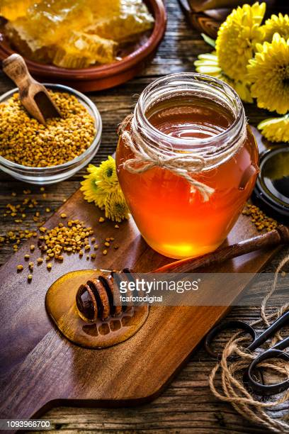honey jar, bee pollen and honeycomb on rustic wooden table - organic compound stock photos and pictures