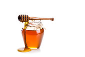 Honey jar with honey dipper isolated on white background