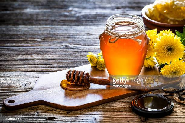 honey jar with honey dipper shot on rustic wooden table - honey stock pictures, royalty-free photos & images