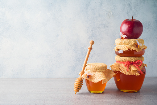 Honey jars and apple over grey background 1167211046