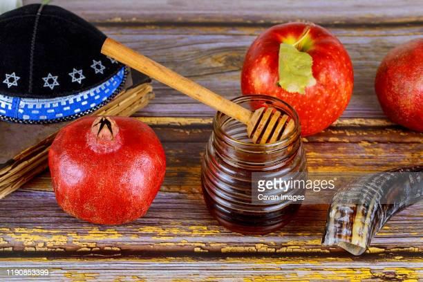 honey on the pomegranate and apples. jewish new year rosh ha shana kippah yamolka and shofar - jewish prayer shawl stock pictures, royalty-free photos & images