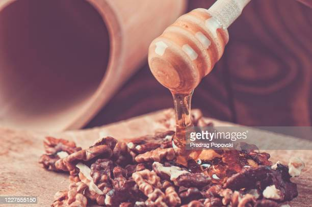honey on wooden spoon and walnuts - kumanovo stock pictures, royalty-free photos & images