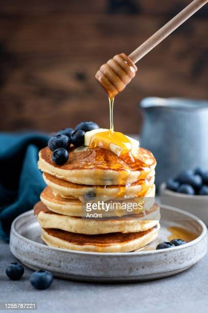 honey pouring on blueberry pancakes - pancakes stock pictures, royalty-free photos & images