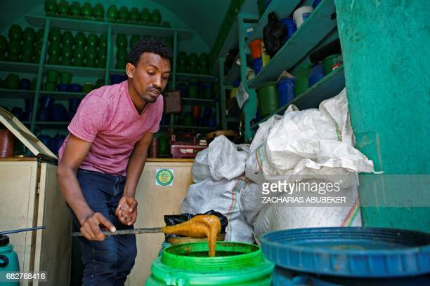 Honey shop keeper Haile Gebru is pictured preparing honey to be sold to customers in Mekele in the Tigray region of northern Ethiopia on March 30...