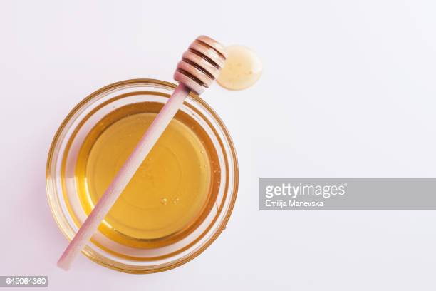 Honey spoon over glass bowl