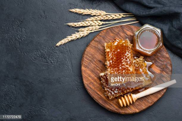 honeycombs and jar of honey on black background - honey stock pictures, royalty-free photos & images