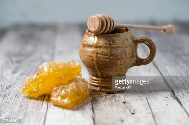 Honeycombs, clay pot and honey dipper on wood