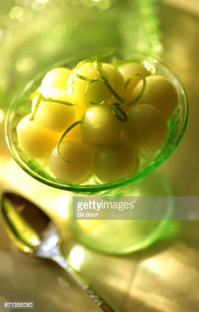 Honeydew melon balls in a dessert dish with lime strips garnish