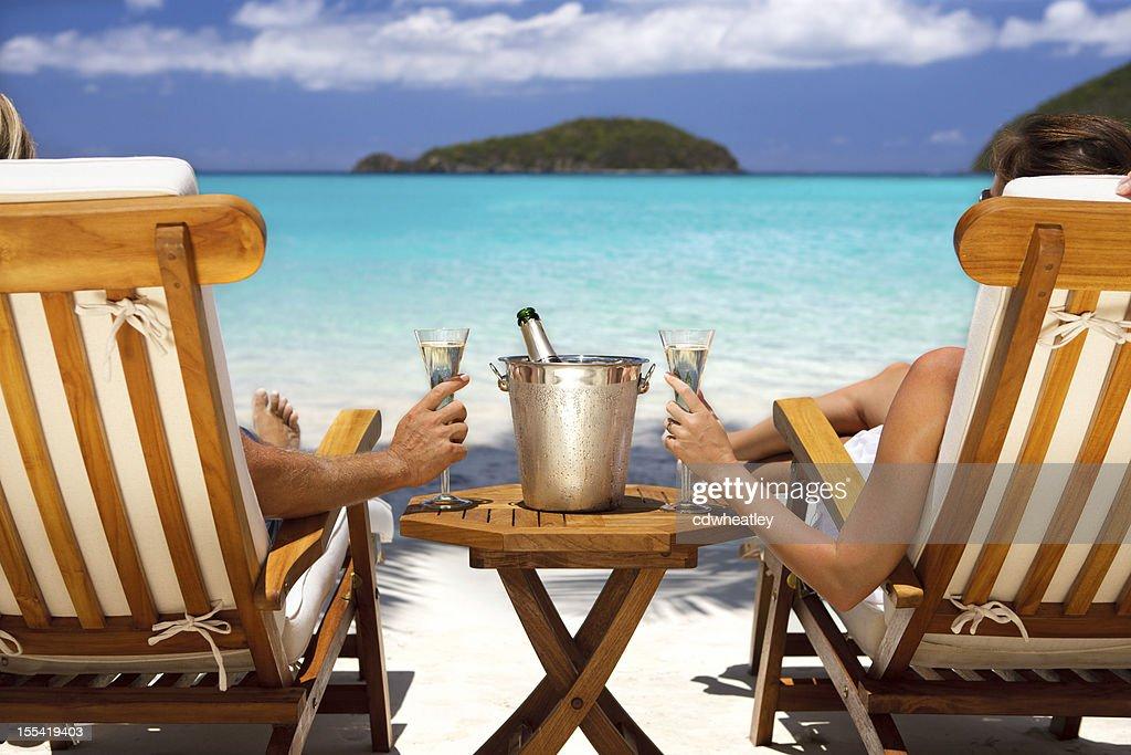 Flitterwochen-Paar auf Liegestühlen trinkt Champagner in der Karibik : Stock-Foto
