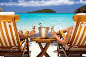 honeymoon couple in recliners drinking champagne at a Caribbean beach