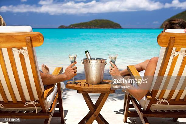 honeymoon couple in recliners drinking champagne at a caribbean beach - perfection stock pictures, royalty-free photos & images