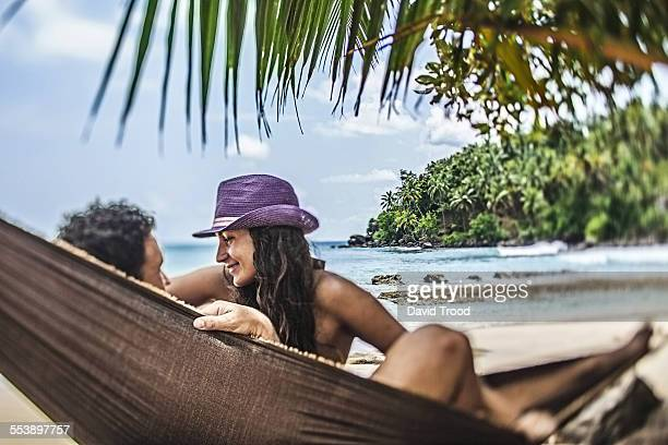 Honeymoon couple relaxing in hammock by the sea.