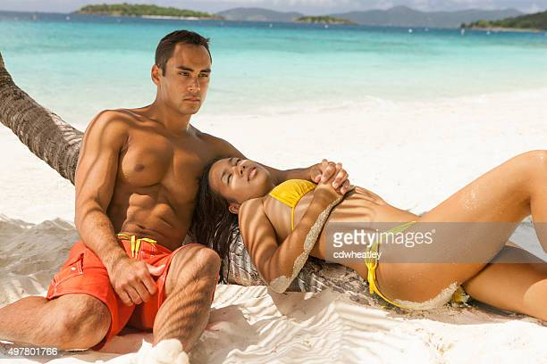 honeymoon couple relaxing under the palm tree at a beach