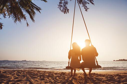 Honeymoon travel, silhouete of couple in love on the beach. 1062126602