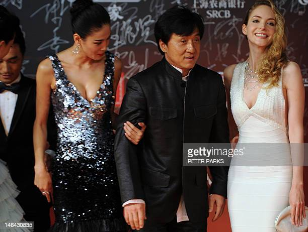Hong Kong action movie star Jackie Chan poses with Laura Weissbecker and Zhang Lan Xin on the red carpet during the opening ceremony for the 15th...
