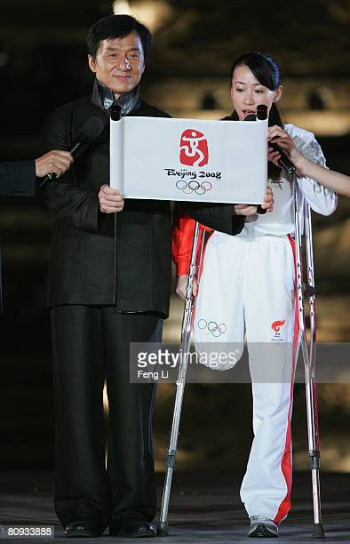 Hong Kong action star Jackie Chan reads a note beside Jin Jing, a Chinese Paralympic fencer who was one of the Paris torchbearers, during the...