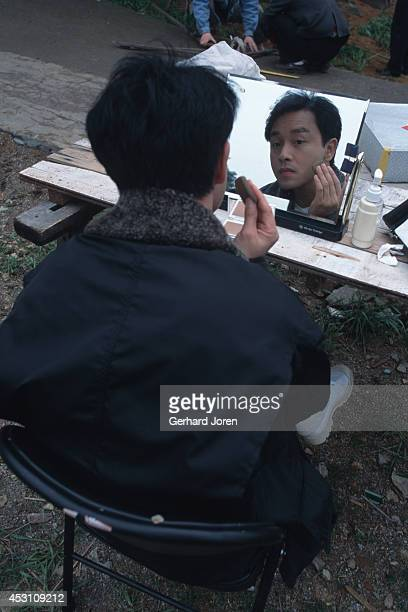 Hong Kong actor Leslie Cheung Kwok Wing putting on makeup during the filming of 'Temptress Moon' in Shanghai Film Studios