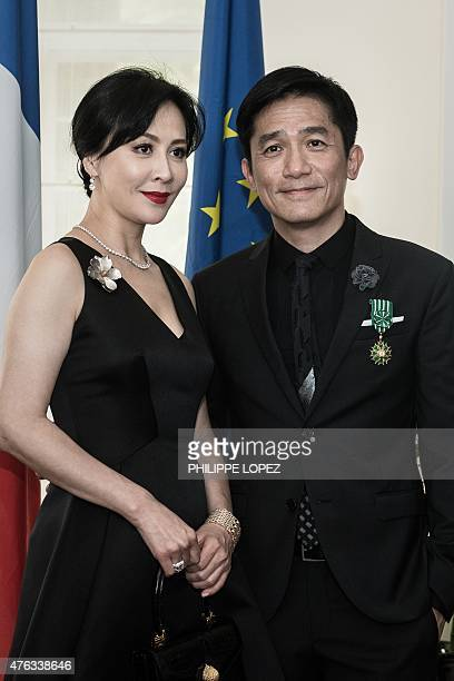 Hong Kong actor Tony Leung poses with his wife Carina Lau after receiving the distinction of Officier de lOrdre des Arts et des Lettres at the French...