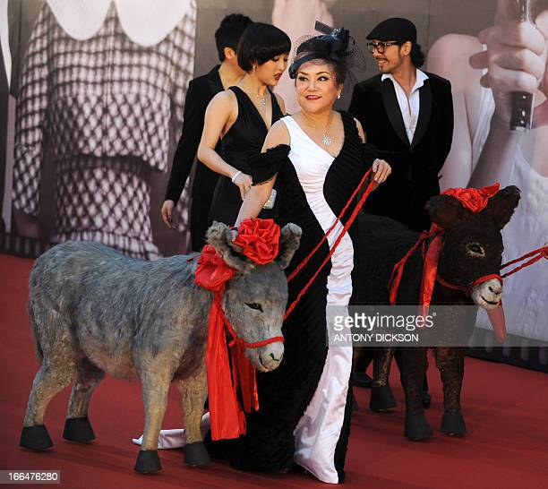Hong Kong actress Susan Shaw poses with a toy donkey for photographers on the red carpet during the 32nd Hong Kong Film Awards on April 13 2013 The...