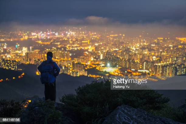 Hong Kong. Backpacker's silhouette with out-of-focus city lights.