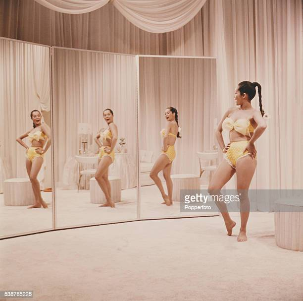 Hong Kong born actress Nancy Kwan pictured wearing a yellow bikini whilst standing in front of three full length mirrors in a dressing room in 1962
