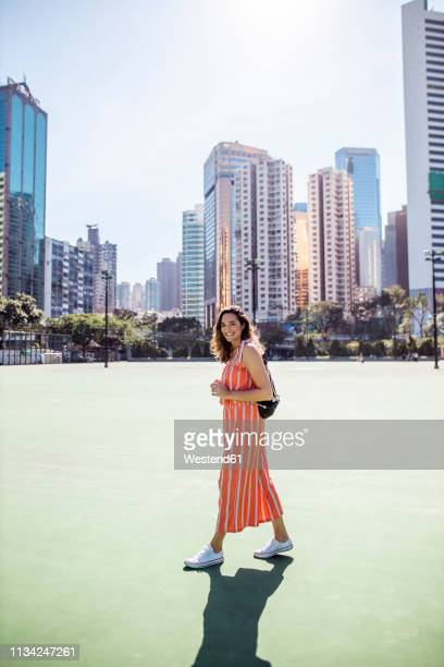 Hong Kong, Causeway Bay, Victoria Park, portrait of smiling woman on a sports field