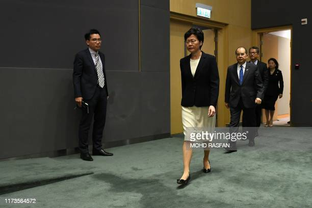 Hong Kong Chief Executive Carrie Lam arrives with her cabinet ahead of a press conference in Hong Kong on October 4, 2019. - Thousands of masked...