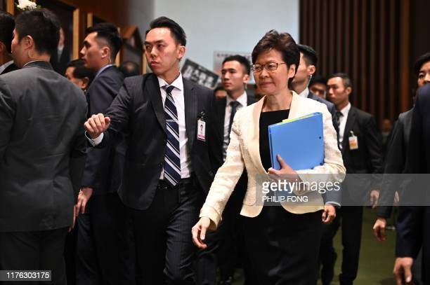 Hong Kong Chief Executive Carrie Lam walks past protesting pro-democracy lawmakers as she arrives for a question and answer session in the...