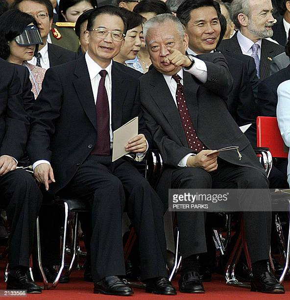 Hong Kong Chief Executive Tung Cheehwa points out something to Chinese Premier Wen Jiabao during the flag raising ceremony to mark the 6th...